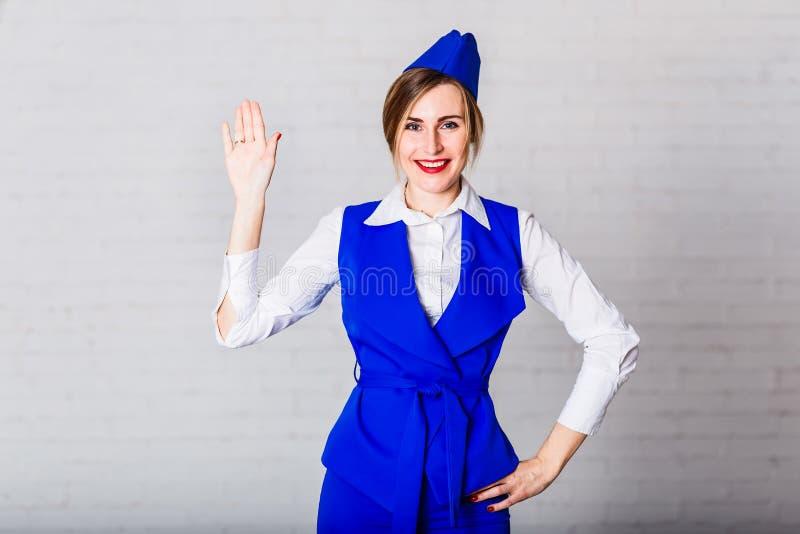 Gladlynt le stewardess i ett blått lock som vinkar hennes hand royaltyfria bilder