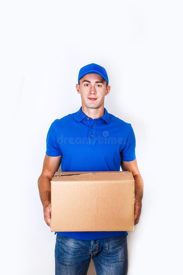 Gladlynt leveransman Lycklig ung kurir som rymmer en kartong och le arkivfoton