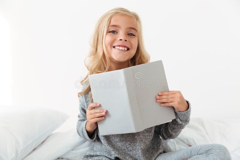 Gladlynt liten flicka i grå pyjamas som rymmer boken som ser ca royaltyfria bilder