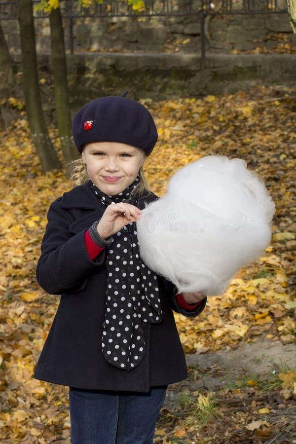 Gladlynt liten flicka som äter bomull royaltyfri bild