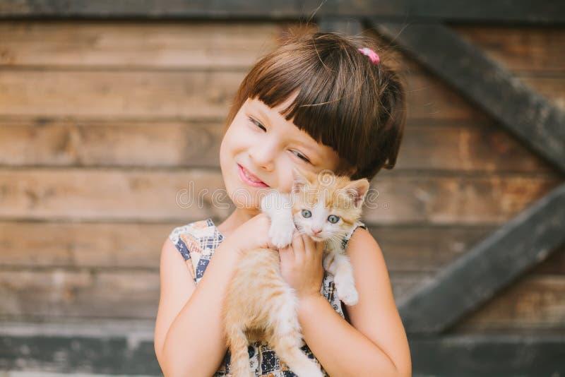 Gladlynt liten flicka som rymmer en katt i henne armar royaltyfria foton