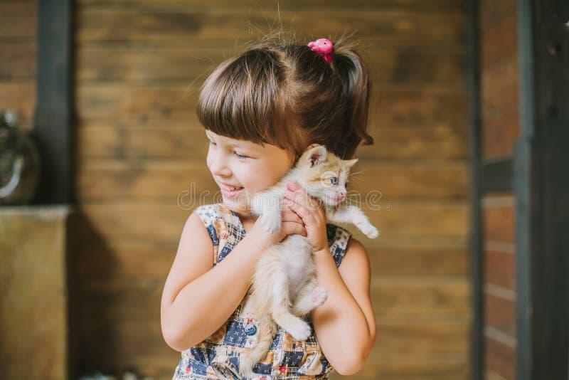 Gladlynt liten flicka som rymmer en katt i henne armar royaltyfria bilder