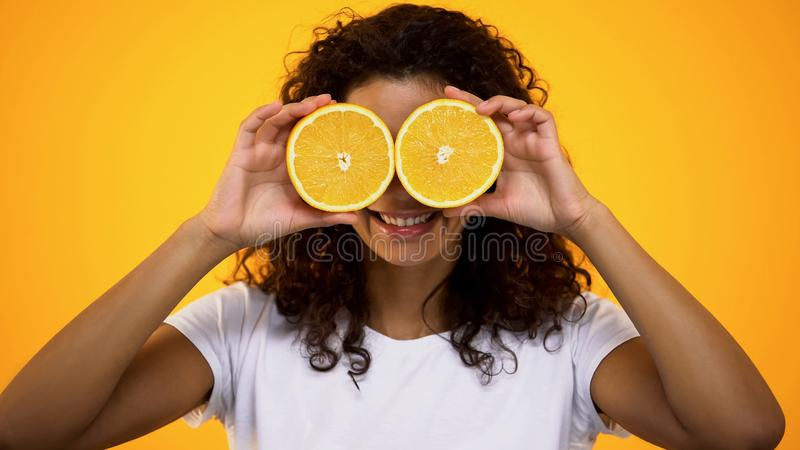 Gladlynt lockig-haired kvinna som rymmer den orange skivaframdelen av ögon och att le arkivbilder