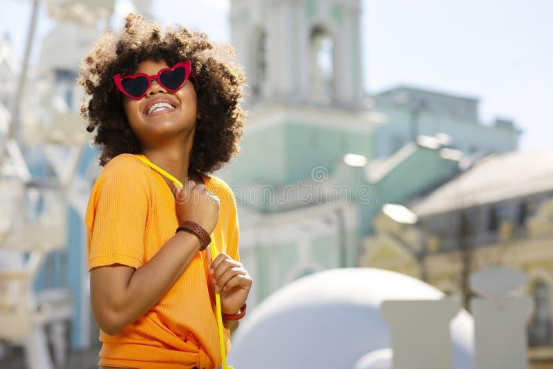 Gladlynt lockig kvinna i hjärta-formad solglasögon som poserar i centrum royaltyfri fotografi