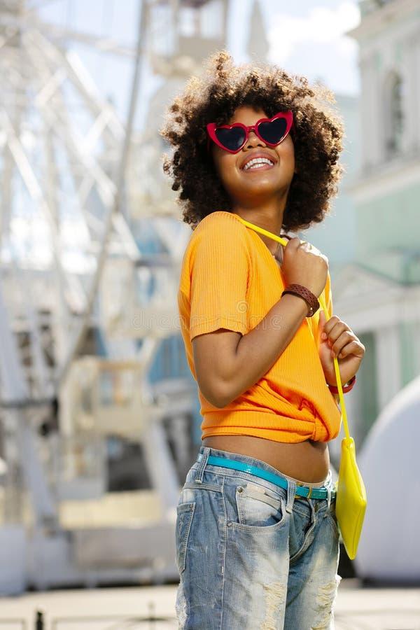 Gladlynt lockig kvinna i hjärta-format grina för solglasögon royaltyfri foto