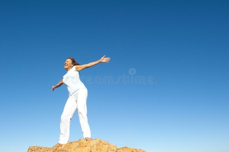 Gladlynt lycklig kvinna på bergöverkant royaltyfri foto