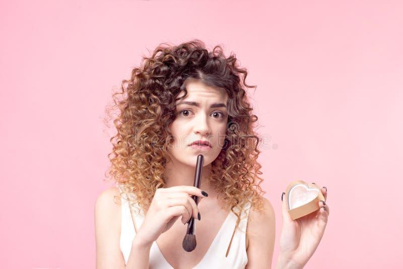 Gladlynt lycklig kvinna som sitter med en makeupborste, medan arbeta i sk?nhetsalongen royaltyfria bilder
