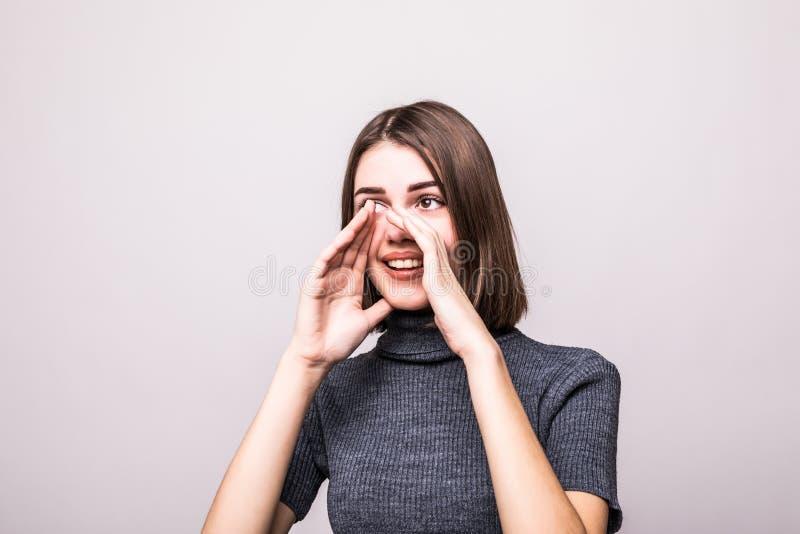 Gladlynt lycklig nätt flicka som ropar skri på grå bakgrund arkivfoto