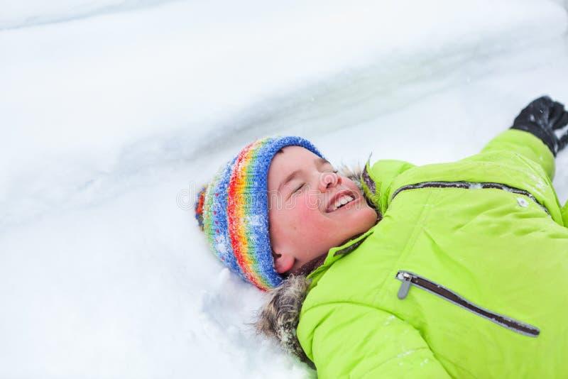 Gladlynt lycklig pojkelögn på snö, royaltyfria bilder