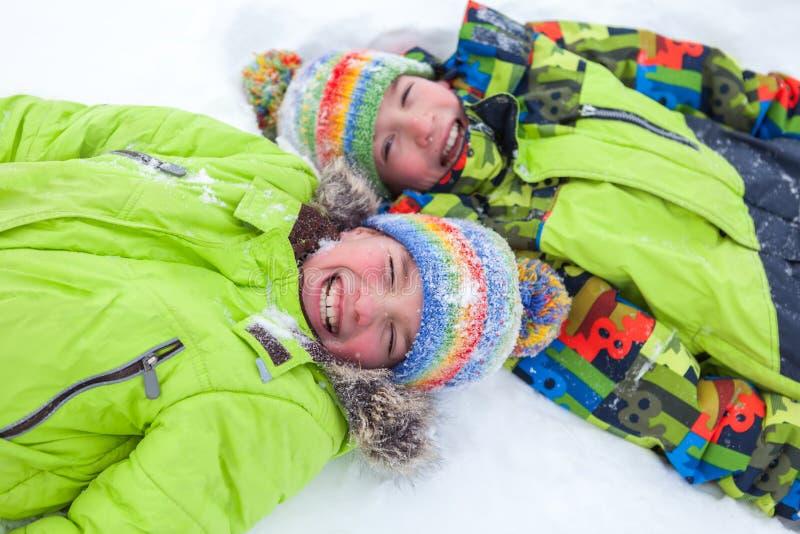 Gladlynt lycklig pojkelögn på snö, arkivbilder