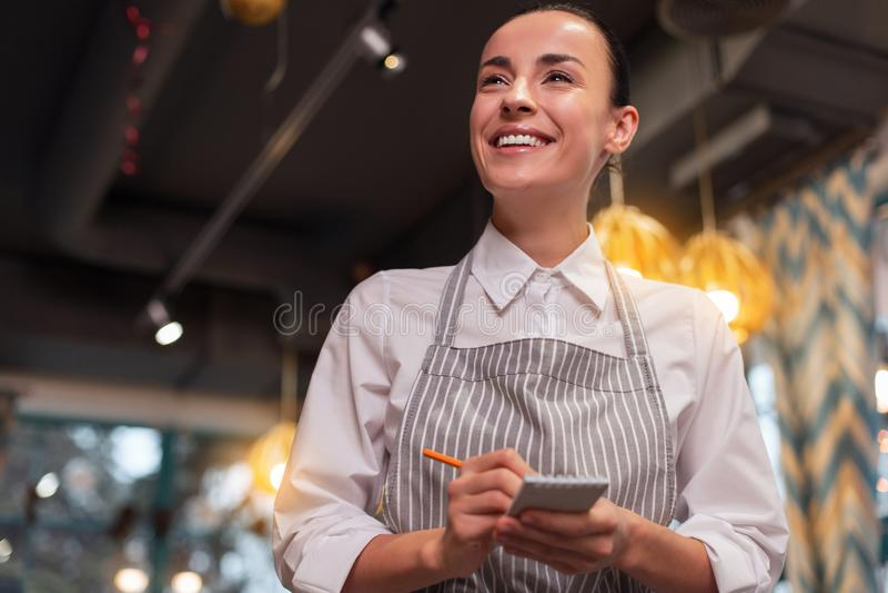 Gladlynt lycklig servitris som ner skriver beställning fotografering för bildbyråer