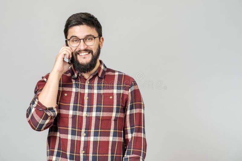 Gladlynt lycklig ung man som skrattar le samtal på telefonen royaltyfri fotografi