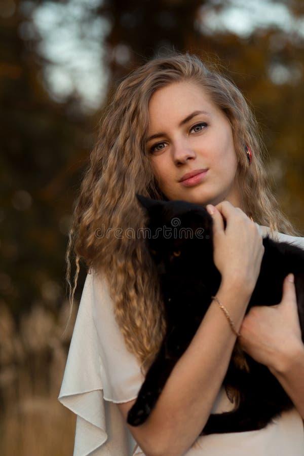 Gladlynt, lyckligt och le flickan med perfekt leendesmekning och den rymda svarta katten i händer i sommar, vår, höstskog, utomhu arkivbild