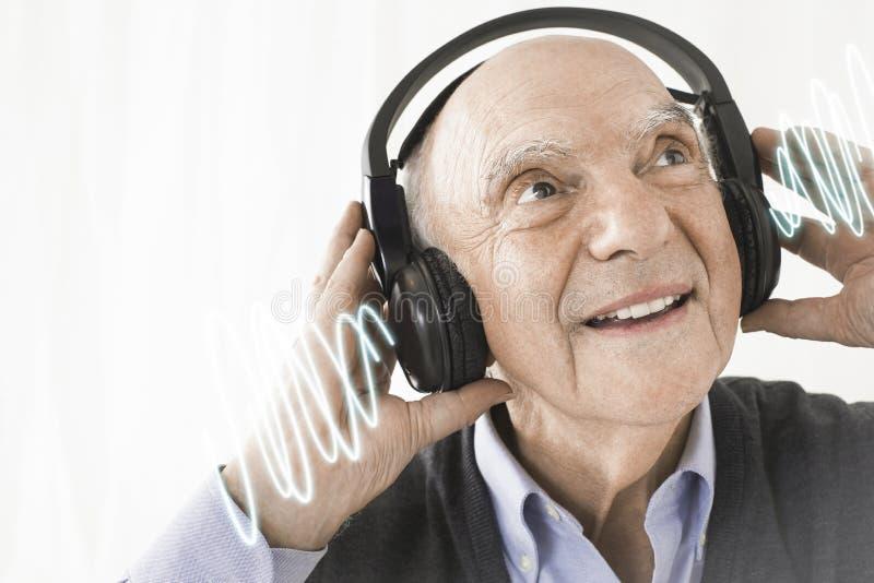 Gladlynt lyssnande musik för hög man till och med hörlurar mot vit bakgrund royaltyfri bild