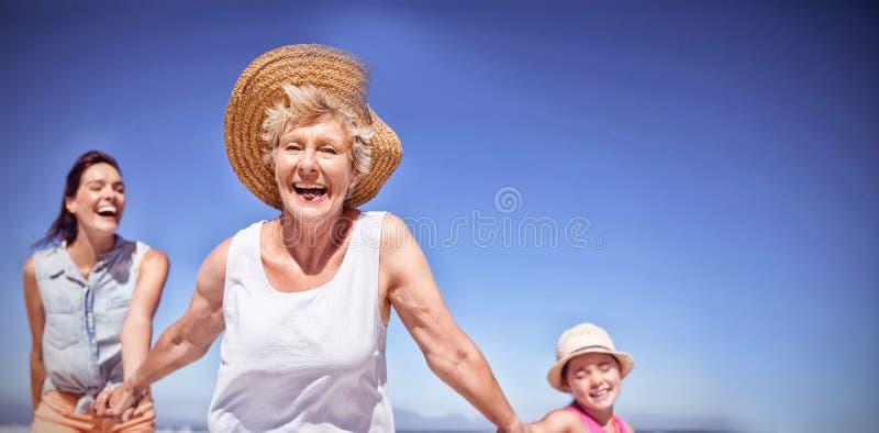 Gladlynt mång--utveckling familj på stranden royaltyfria foton