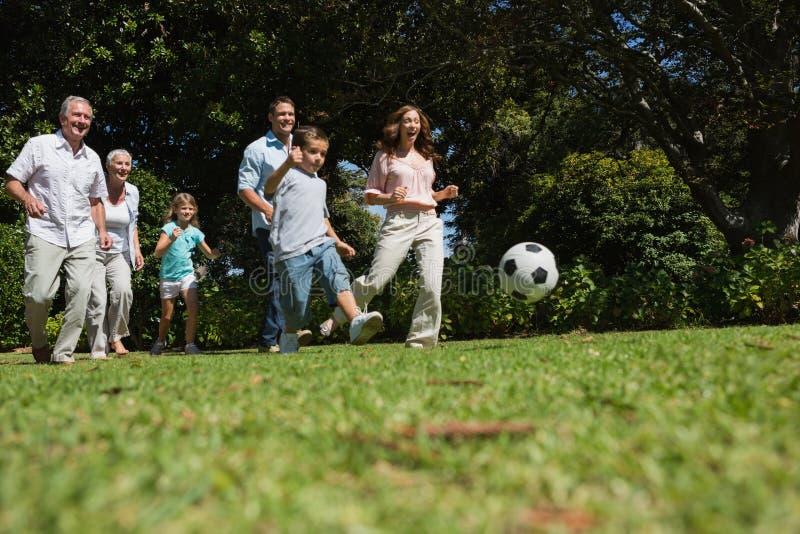 Gladlynt mång- utvecklingsfamilj som spelar fotboll fotografering för bildbyråer