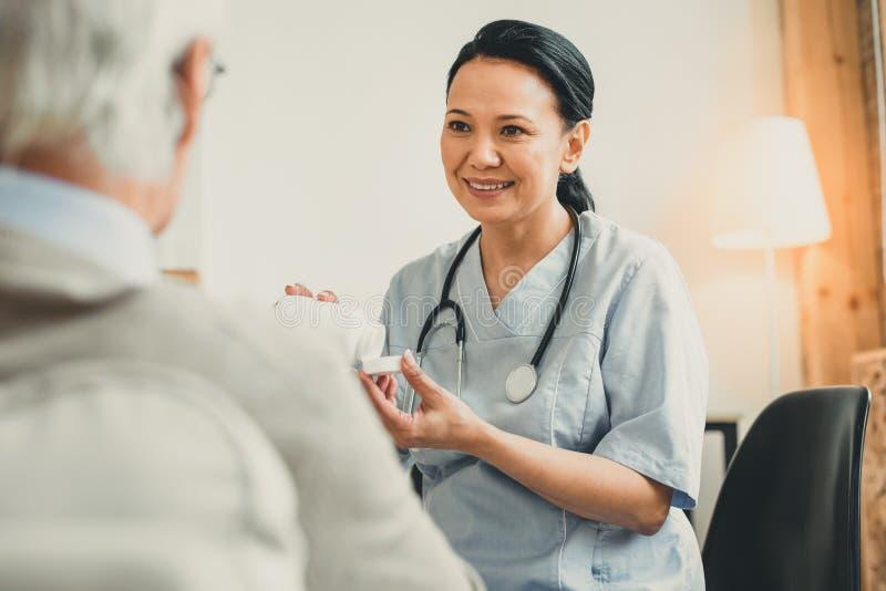 Gladlynt mörker-haired doktor som framlägger nya mediciner till hennes patient royaltyfri foto