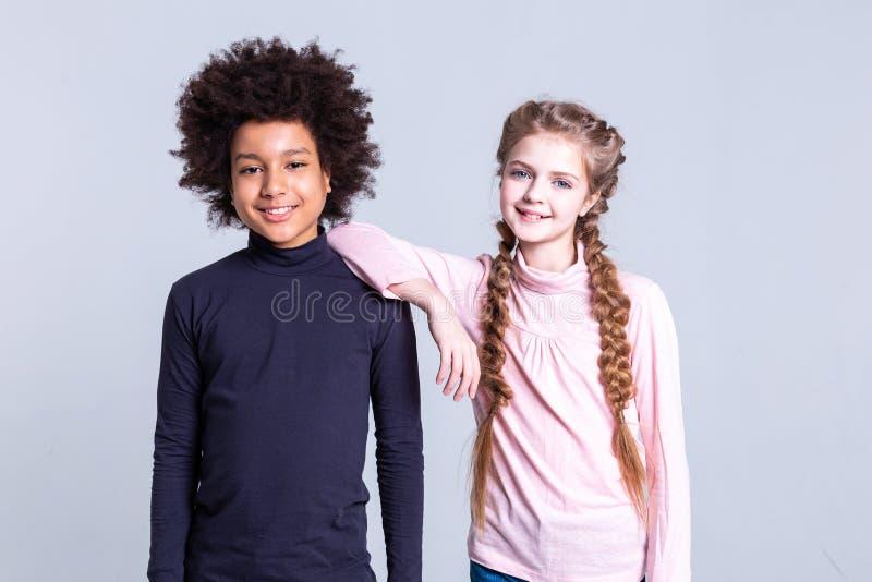 Gladlynt mörker-haired pojke med löst frisyranseende nära flicka fotografering för bildbyråer