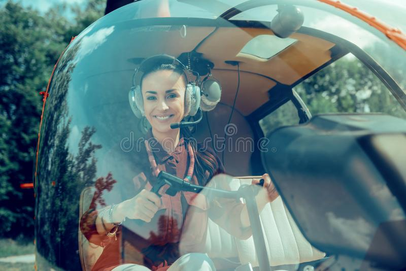 Gladlynt mörker-haired yrkesmässig pilot som sitter på framsätet arkivbilder