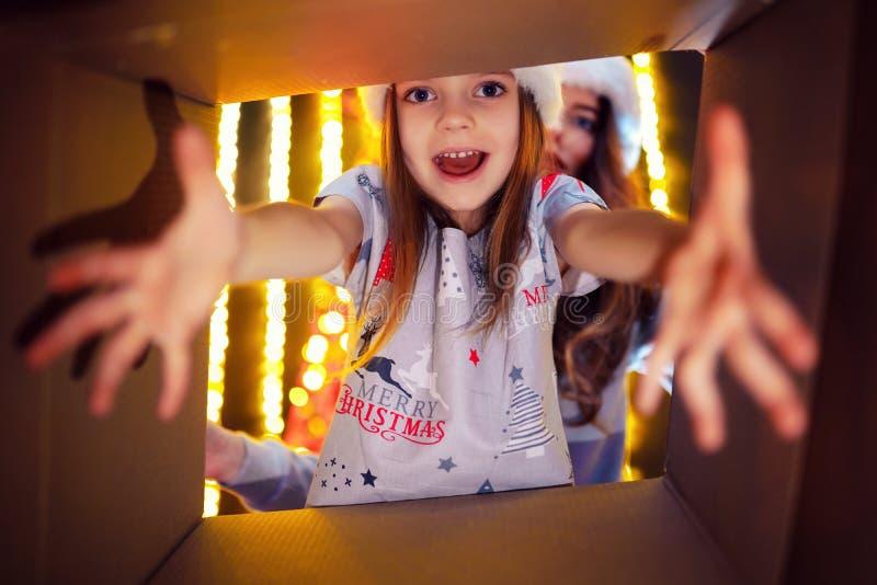 Gladlynt mamma för glad jul och för lyckliga ferier och hennes gullig dotterflicka som öppnar en julklapp Förälder och royaltyfria bilder