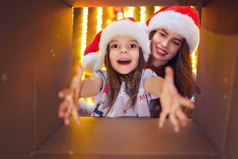 Gladlynt mamma för glad jul och för lyckliga ferier och hennes gullig dotterflicka som öppnar en julklapp Förälder och fotografering för bildbyråer