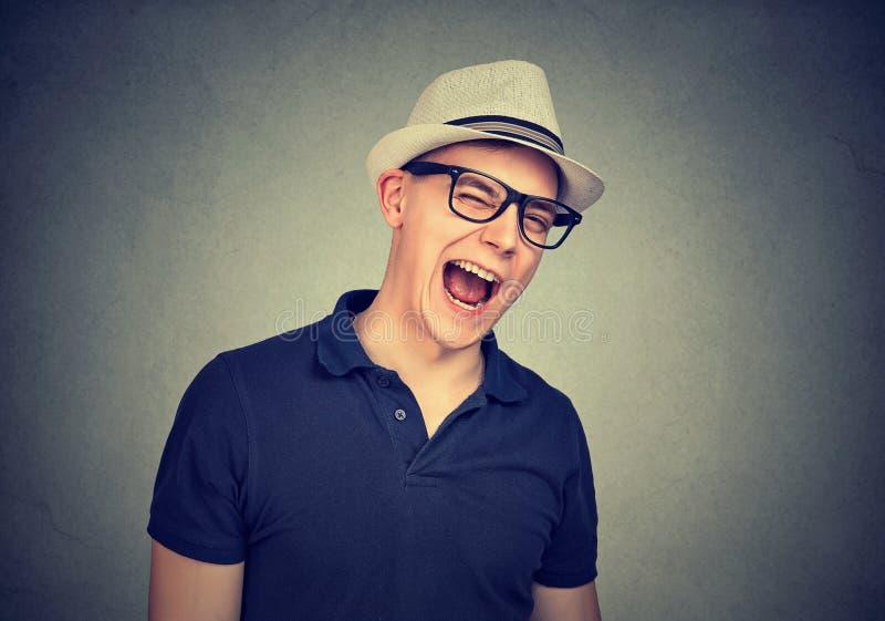 Gladlynt man i en vit hatt som blinkar över grå väggbakgrund royaltyfri foto