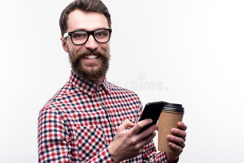 Gladlynt man i glasögon som smsar, medan ha kaffe fotografering för bildbyråer