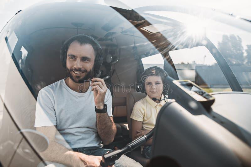 Gladlynt man och pojke som kör rotornivån fotografering för bildbyråer