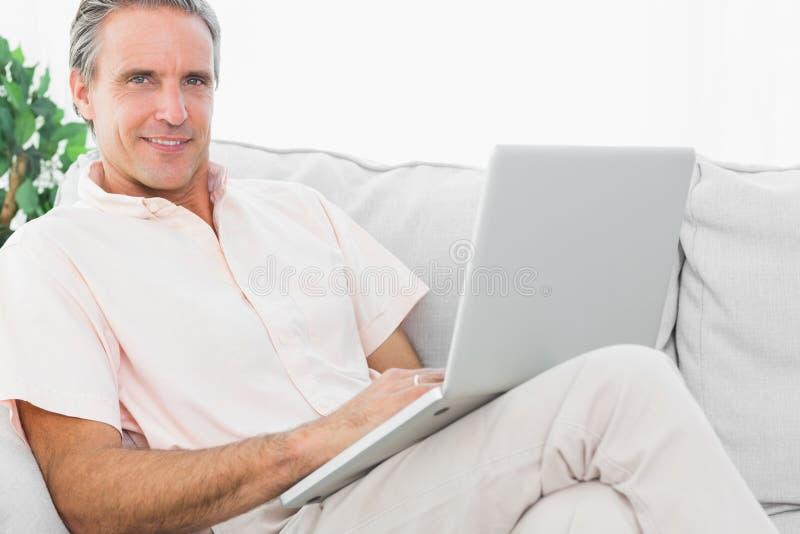 Gladlynt man på hans soffa genom att använda bärbara datorn som ser kameran royaltyfria bilder