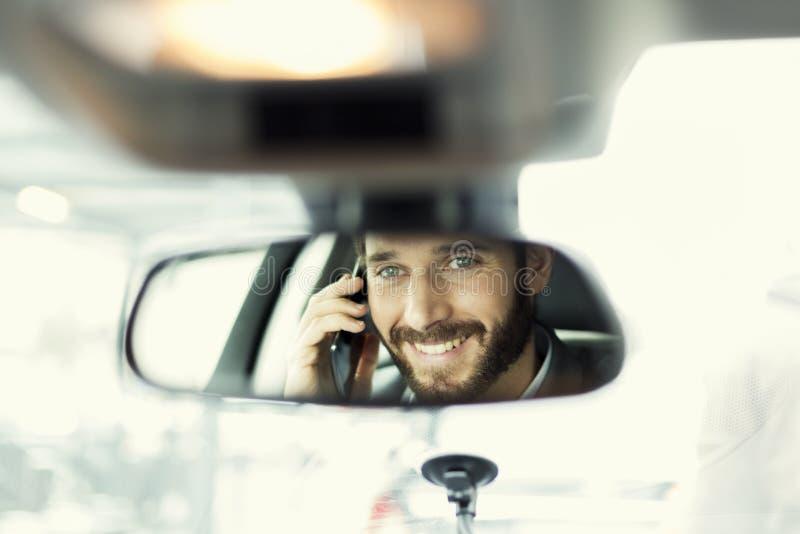 Gladlynt man på mobiltelefonen i bilen Reflexion i spegeln royaltyfri foto