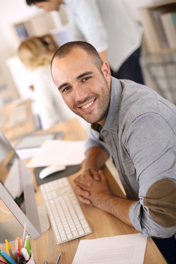 Gladlynt man som använder datoren på kontoret arkivfoto
