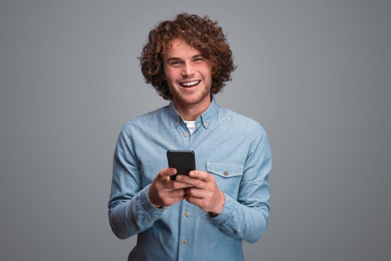 Gladlynt man som använder smartphonen arkivbild