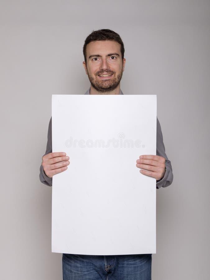 Gladlynt man som framlägger en vit papp royaltyfri fotografi