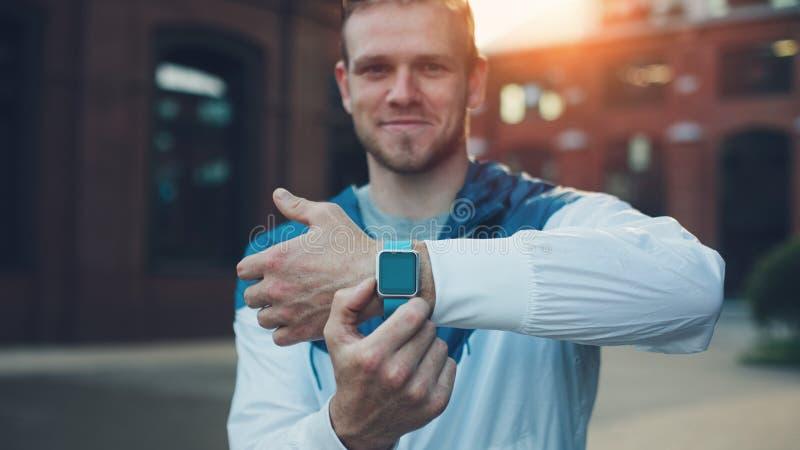 Gladlynt man som visar hans smarta klockor på handleden fotografering för bildbyråer