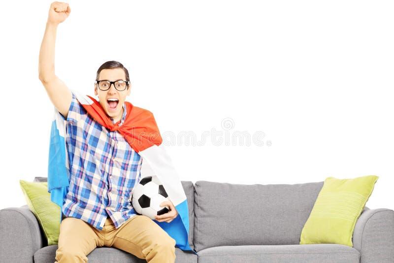 Gladlynt manlig sportfan med fotbollbollen och den hållande ögonen på sporten för flagga royaltyfri fotografi