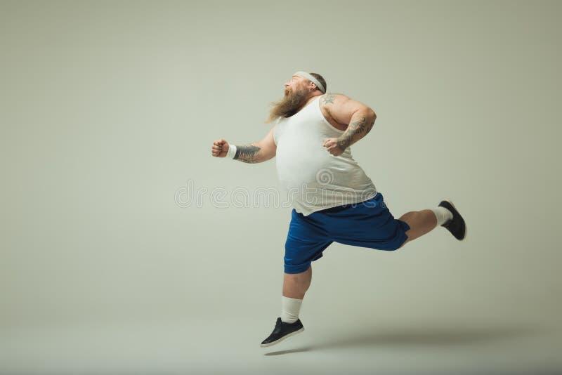 Gladlynt manlig tjockis som joggar med spänning royaltyfria foton