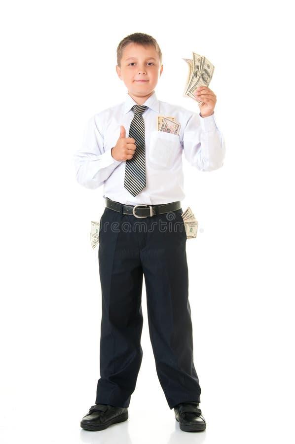 Gladlynt manlig tonåring för pojkestudentskolpojke som rymmer pengar isolerade på en vit bakgrund Barnaffärsman, första förtjänst royaltyfria bilder