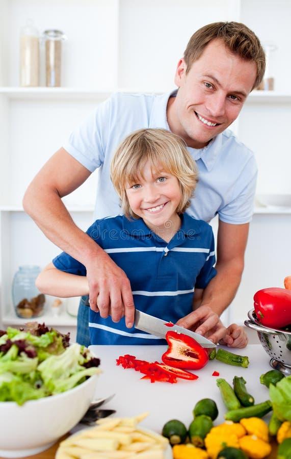 gladlynt matlagningfader hans son royaltyfri fotografi