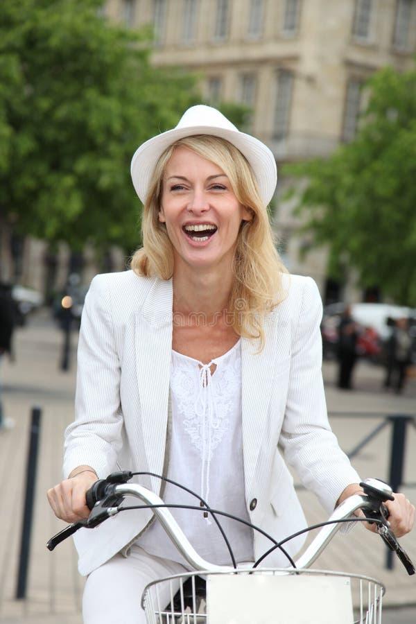 Gladlynt medelålders cykel för kvinnaridningstad som har gyckel royaltyfria bilder