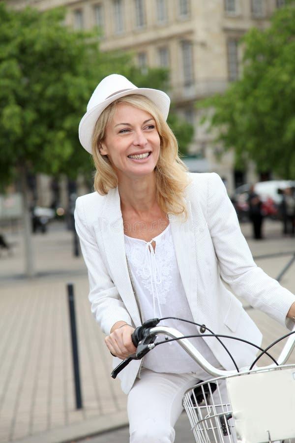 Gladlynt medelålders kvinna som cyklar i stad royaltyfria bilder
