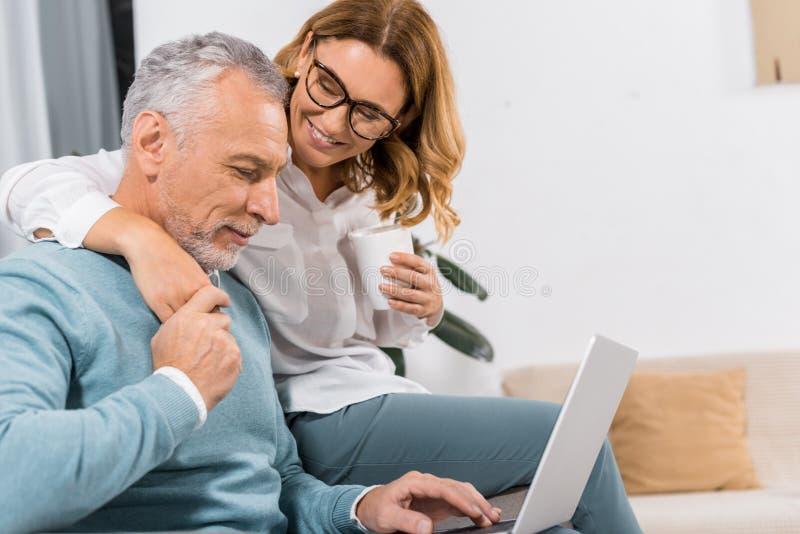 gladlynt mellersta åldrig man som använder bärbara datorn medan hans le fru som nära sitter med kaffe royaltyfri foto