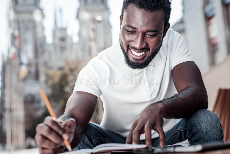 Gladlynt millennial grabb som ler, medan skriva något ner royaltyfri foto
