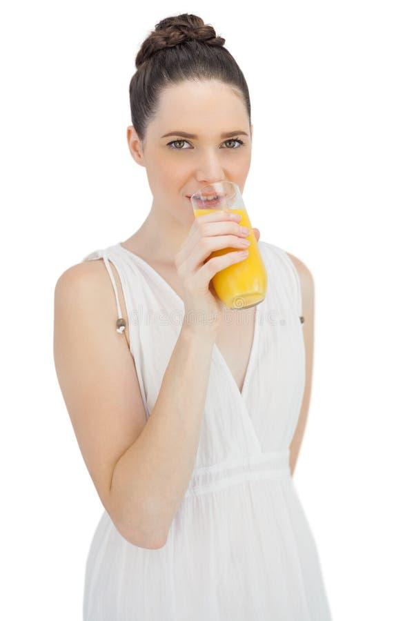 Gladlynt modell i den vita klänningen som dricker orange fruktsaft royaltyfria bilder