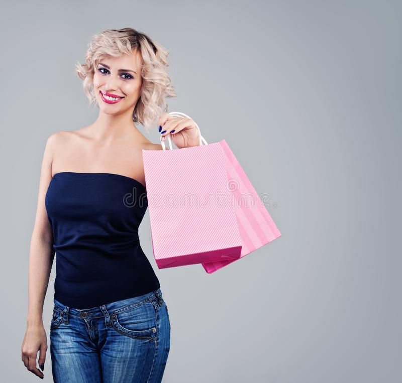 Gladlynt modell som rymmer shoppingpåsar Nätt kvinna med makeup och blont lockigt hår royaltyfri foto