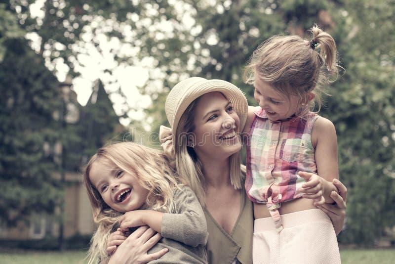 Gladlynt moder med hennes utomhus- döttrar royaltyfria foton