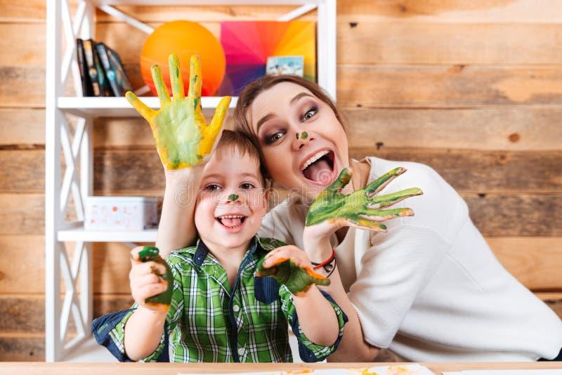 Gladlynt moder och son med målade händer som har gyckel tillsammans royaltyfria bilder