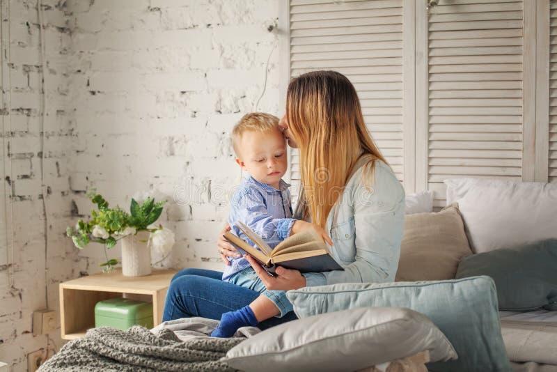 Gladlynt moder och son som hemma läser en bok royaltyfri fotografi