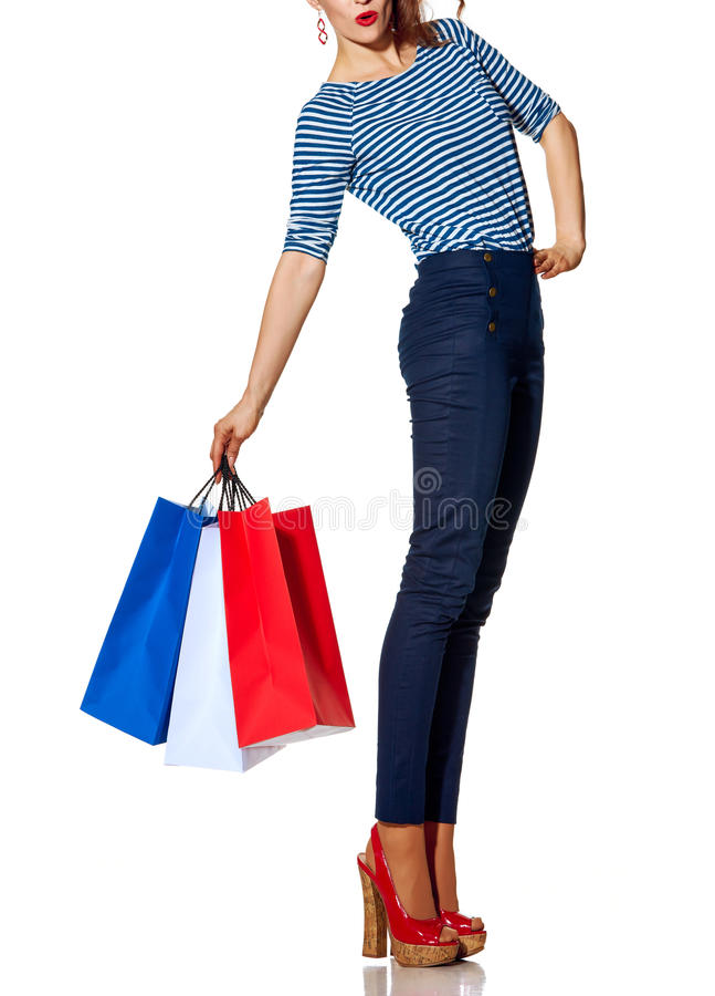 Gladlynt moderiktig kvinna med shoppingpåsar på vit bakgrund royaltyfria bilder