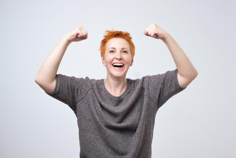 Gladlynt mogen kvinna som ler med lyftta nävar som visar henne styrka och realitetlynne royaltyfri fotografi