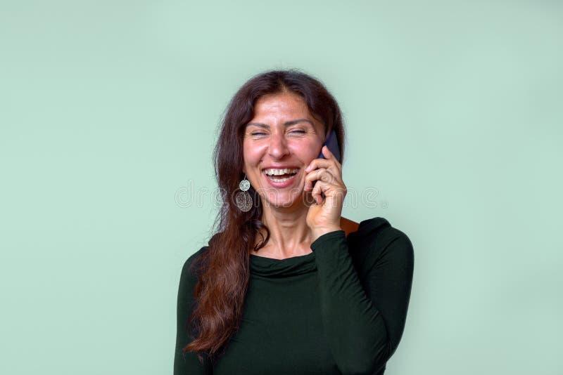 Gladlynt mogen kvinna som talar på mobiltelefonen fotografering för bildbyråer